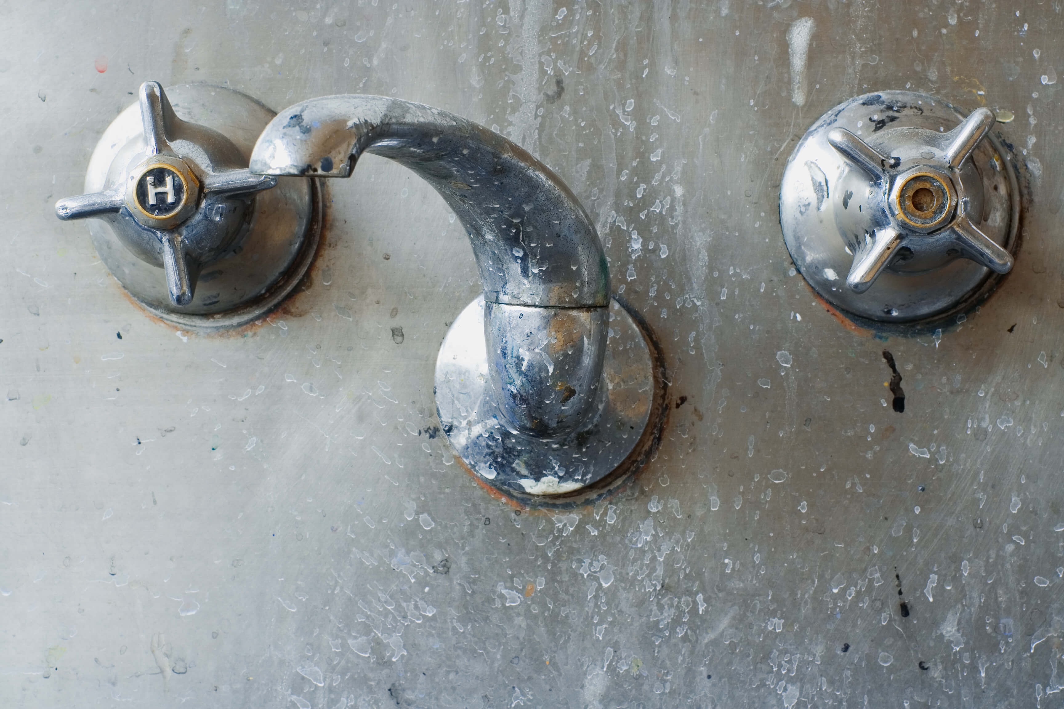 close up of a tap set set in a stainless steel sink or trough. Colorfully grungy and disgusting.