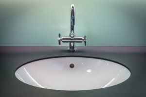 Silver faucet with blue green background. Tips for summer plumbing maintenance